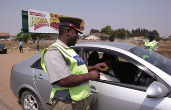 An officer checks a motorist's driver's licence at a checkpoint: File Picture