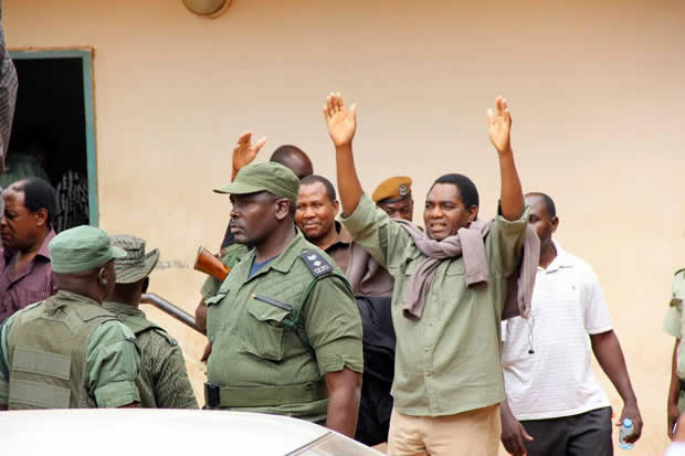 UPND leader Hakainde Hichilema wavws at supporters as he was being taken back to Lusaka Central Prison after appearing at Lusaka's Magistrates Court-picture by Tenson Mkhala
