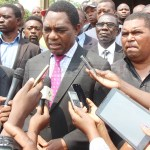 UPND leader Hakainde Hichilema speaks to journalists shortly after attending  the requiem mass for late freedom fighter Mama Chibase Kunda as his vice Geoffrey Mwamba and Lusaka Province youth chairperson Obvious Mwaliteta listen on November 3, 2018 – Picture by Tenson Mkhala