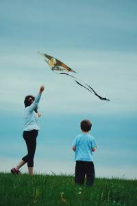 adult and kid playing with kite