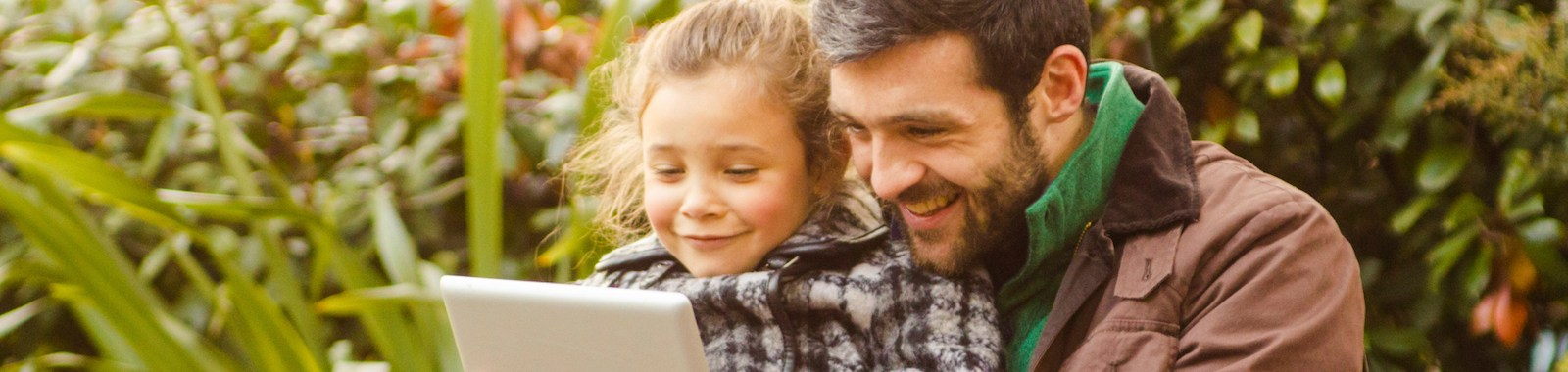 Father And Daughter Using Tablet Sitting On A Bench