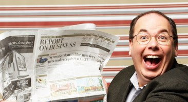 Excited man with newspaper