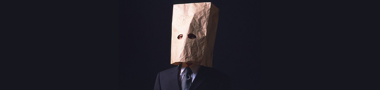 A businessman with paper bag covering head, Front View