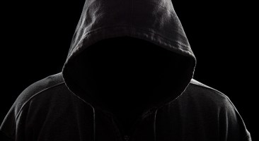 A dark and sinister figure in a hood against black.