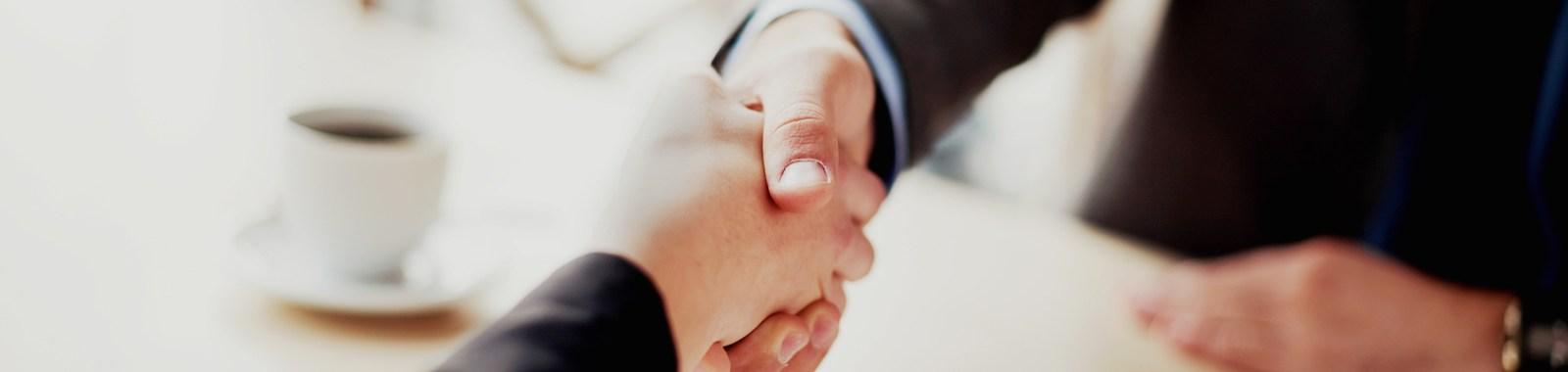 Handshake closeup of businesswoman and businessman.