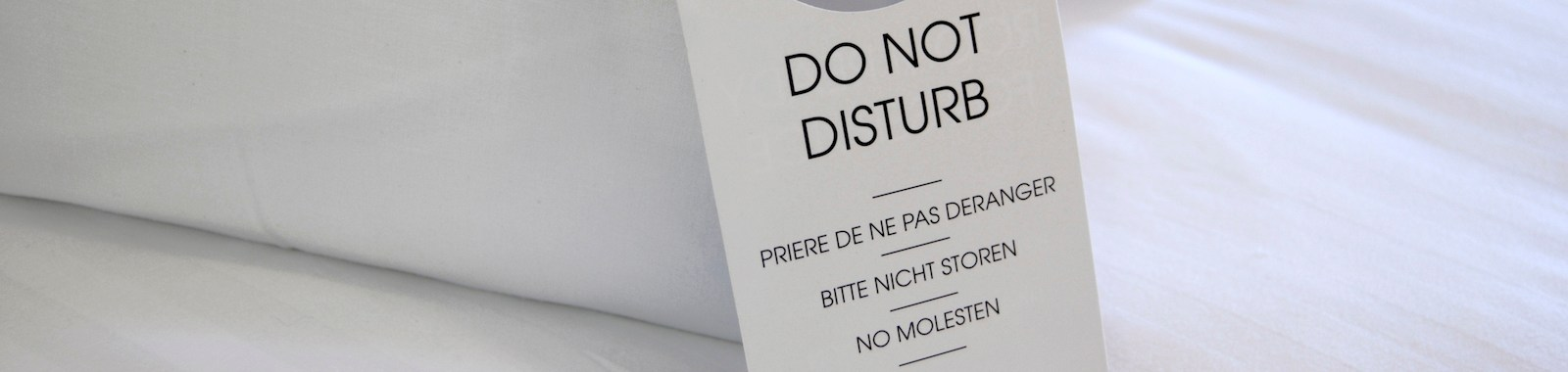 Do Not Disturb Sign on a crisp white bed with the message in French and German as well