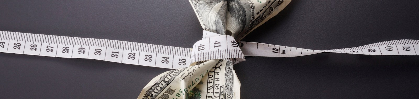 close up of the us currency and tape measure
