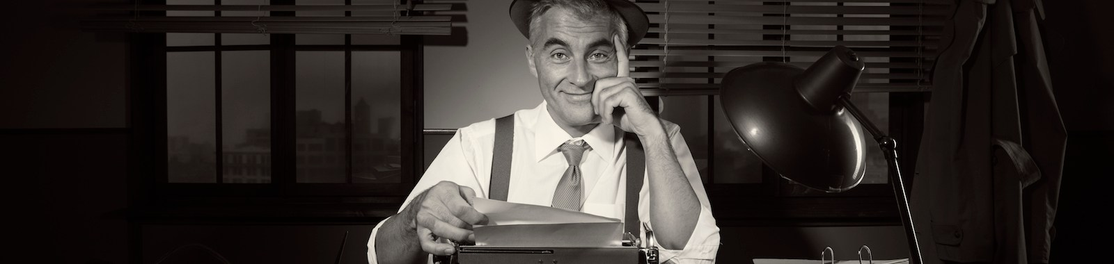 Confident journalist sitting at his desk working late at night with vintage typewriter.
