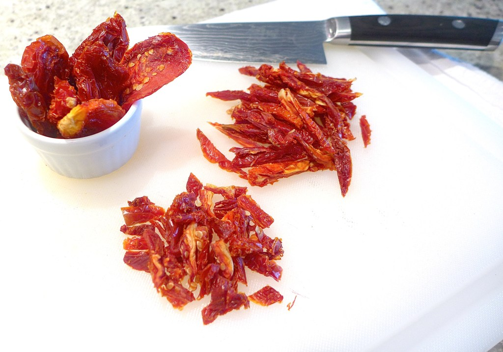 Slice sun-dried tomatoes into ribbons, then chop ribbons into cubes or rectangles.