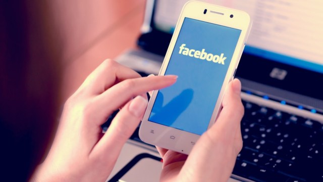 female hands in front of a laptop using a smartphone with the facebook logo showing.