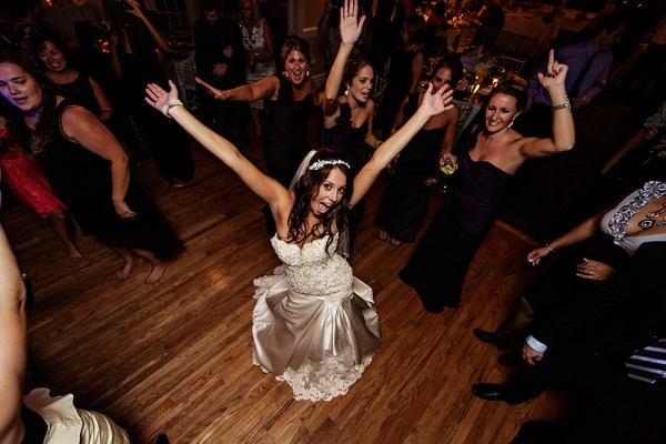 When the dancing started I decided I wanted something different. I mounted a 5D Mark III on a monopod with 14mm lens. a flash was mounted on the camera with the head aimed at the ceiling for bounce. Using a remote release, I got the bride's attention and waited for her reaction, firing when I saw it.