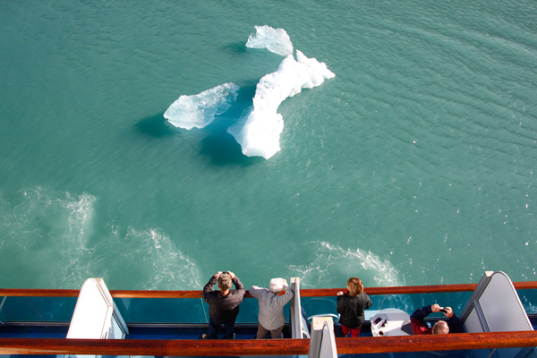 tourists looking at an iceberg from a ship