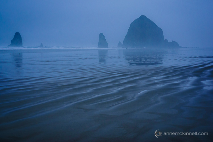 Cannon Beach, Oregon in the fog with sand ripples in the foreground to create depth