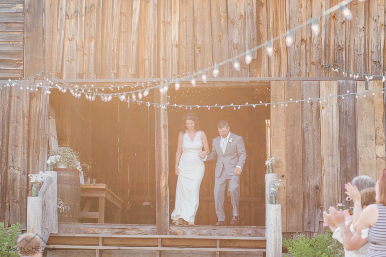 wedding couple coming out of a barn