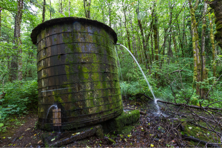 Old water storage tank overflowing and leaking