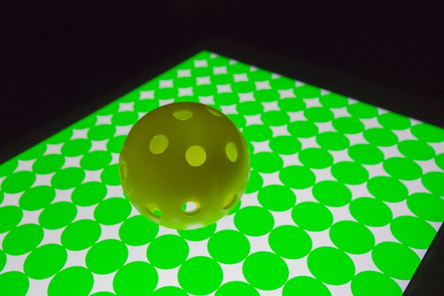 yellow-ball-on-green-circles-background