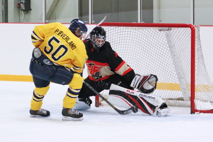 A hockey player tries to deke around the goaltender