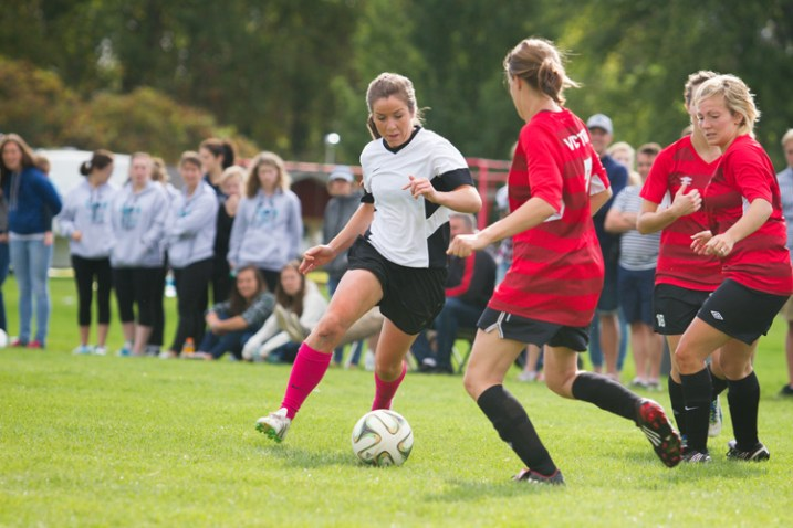A female soccer player attempts to dribble the ball through two defenders