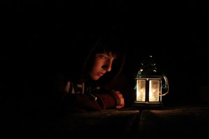 A boy looking at a lantern, where the photo has been taken in low light