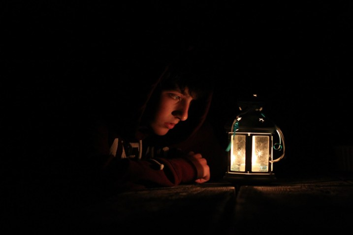A boy looking at a lantern, where the photo has been taken in low light - capture the mood and atmosphere