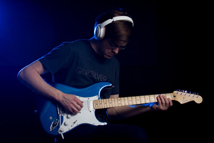 A man plays guitar with a burst of blue color from the flash behind him