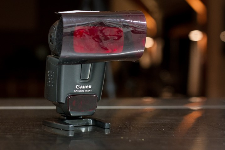 A red colored gel filter covering an off-camera flash unit