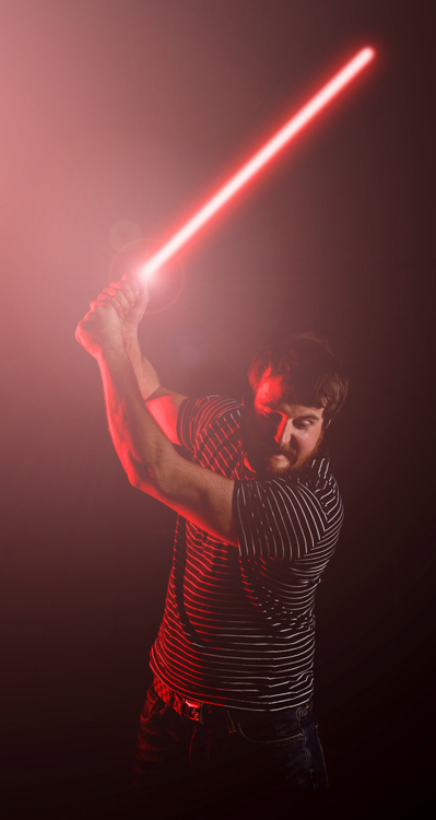 An image of a man with a lightsaber, made possible through a red colour placed over an off-camera flash unit