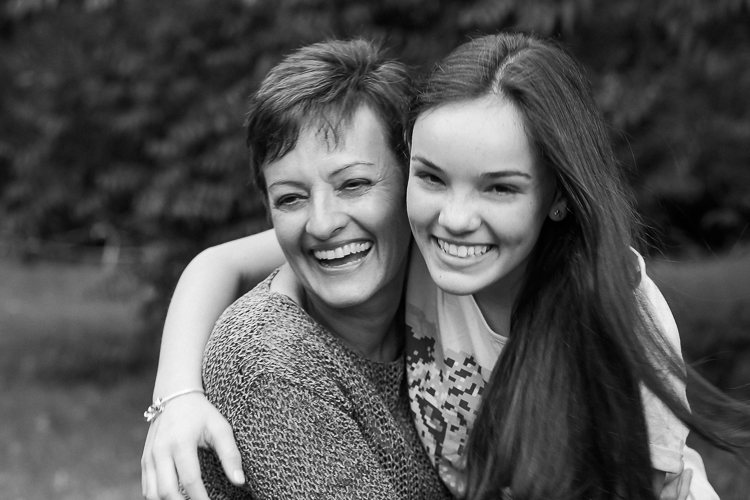 Teen girl and mother embracing and laughing, illustrates letting go of perfectionism