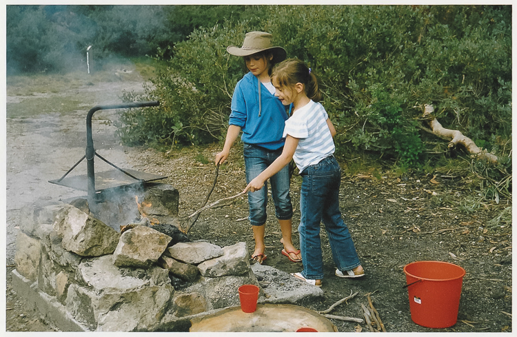 Image shows two gilrs at camp fire, illustrates letting go of perfectionism