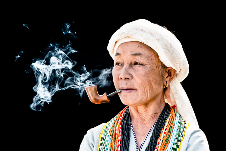 KAren Woman Smoking Her Pipe against a black background