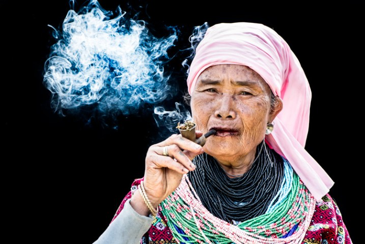 Senior Pwo Karen woman smoking a pipe against a black background - How to Use a Reflector