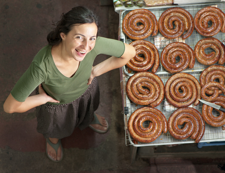 Looking down at a woman standing next to traditional northern Thai sausages at a market. How To Use A Small Soft Box With Your Flash To Transform Your Portraiture