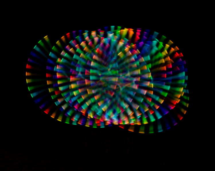 Image: Fire dancer using a colored light bar and taken with a longer exposure to capture the spinnin...