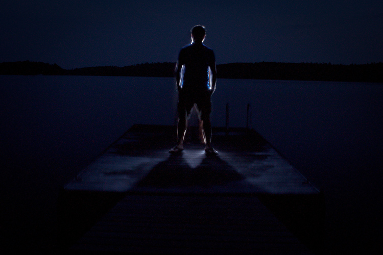 A nighttime portrait of a man on a dock, photographed with central composition