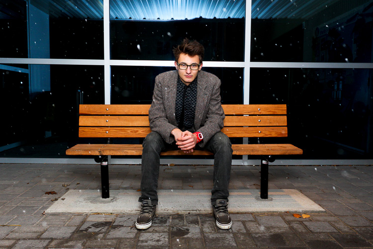 Portrait of man sitting at a bench, photographed with center composition and off-camera flash - How to Break the Rules with a central composition