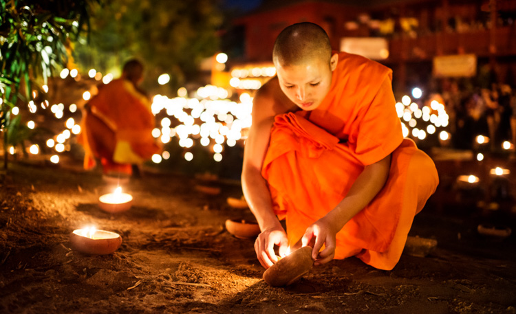 Buddhist monk lighting a candle taken during a Chiang Mai Photo Workshop