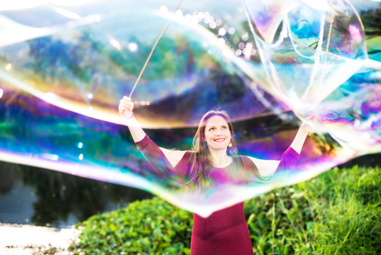 Woman making giant soap bubbles in a park. - How Slow Photography Can Help You Improve Your Images