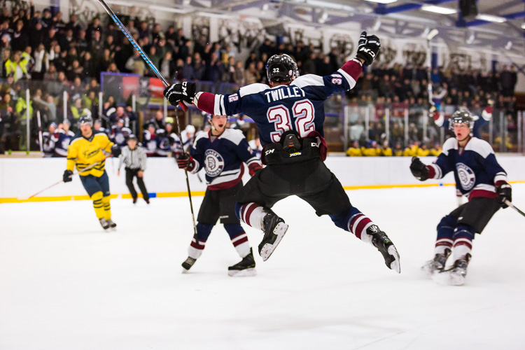 A hockey player jumping into the air in celebration after scoring the winning goal - Tips for Editing Hockey Photos in Lightroom