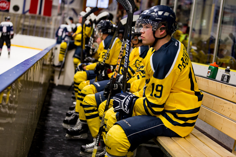 A hockey player sitting on the bench during a game