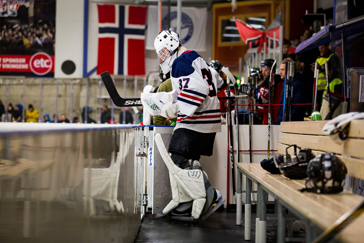 A hockey goalie exits the bench and goes out onto the ice at the start of the game