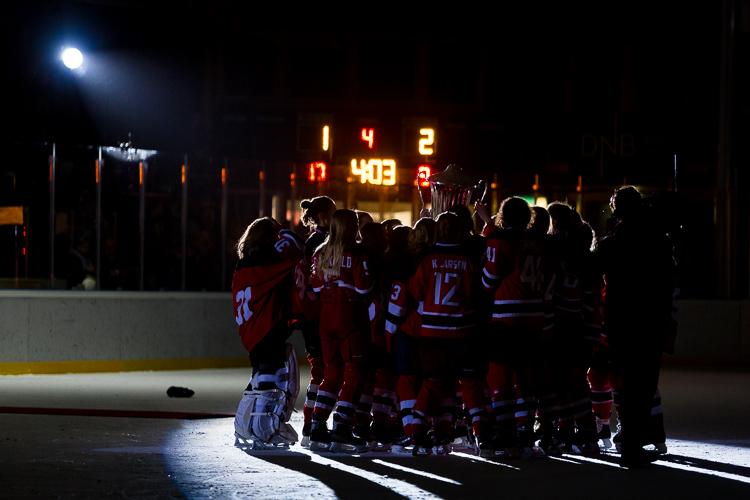 A hockey team celebrates winning the trophy
