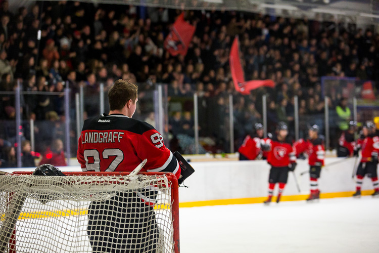 A hockey goaltender taking a break while the crowd cheers - Tips for Editing Hockey Photos in Lightroom