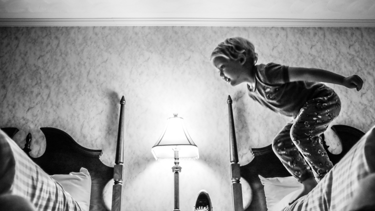 A boy jumping across motel beds. How to Photograph Your Family Vacation