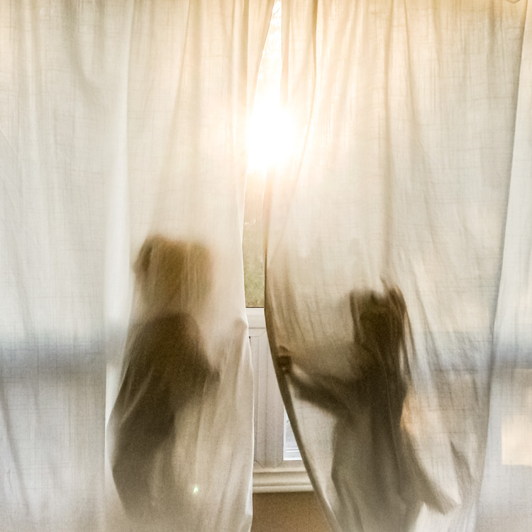 A silhouette of two children playing in curtains. - family life