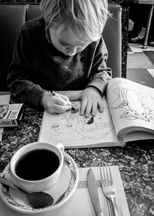 一个孩子在一家餐馆着色。家庭生活