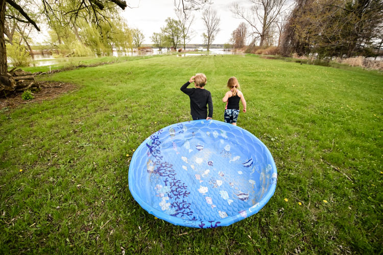 Two kids using a swimming pool as a boat. family life
