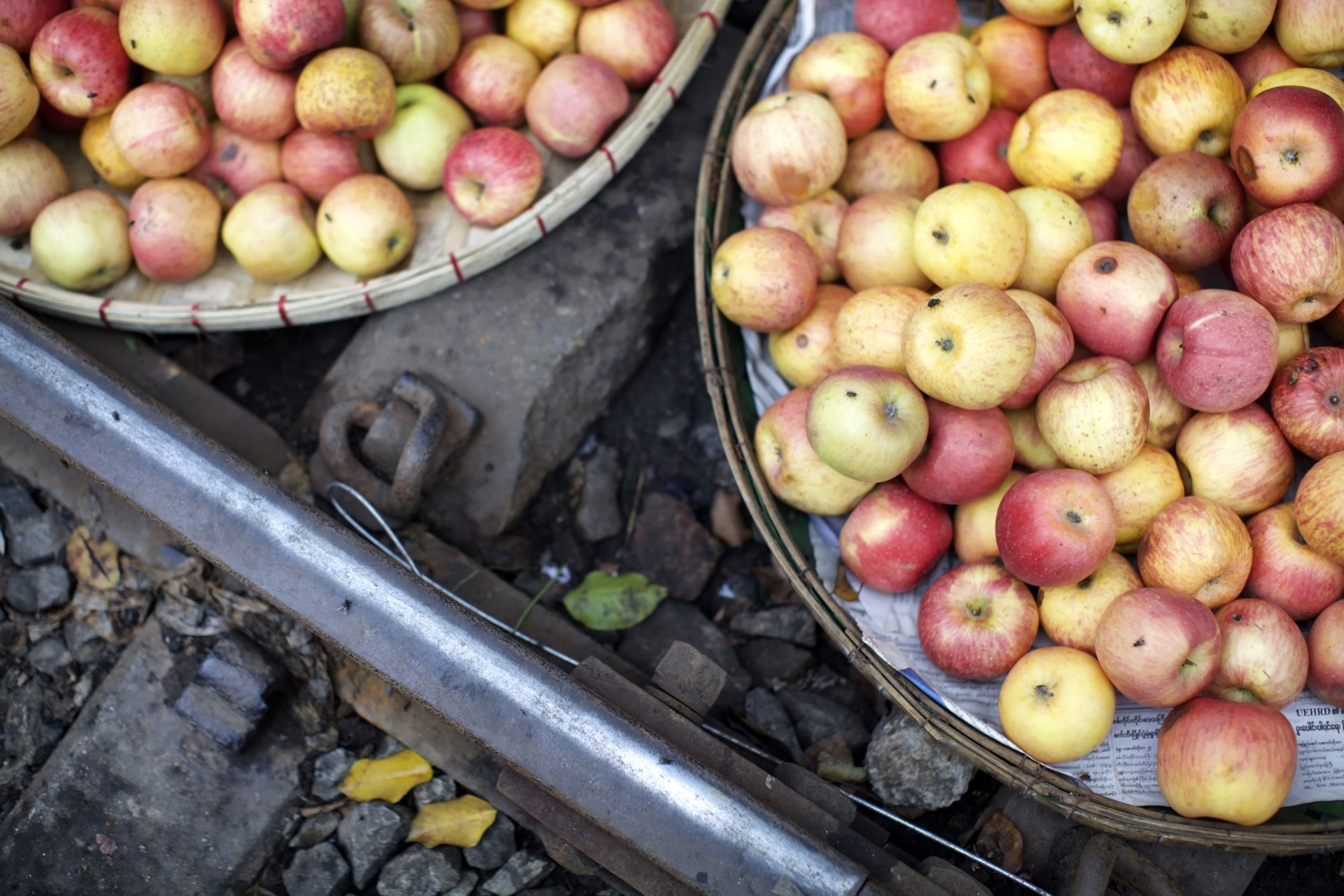 apples in baskets next to train tracks - Five Essential Shots You Need to Get for Street Market Photography
