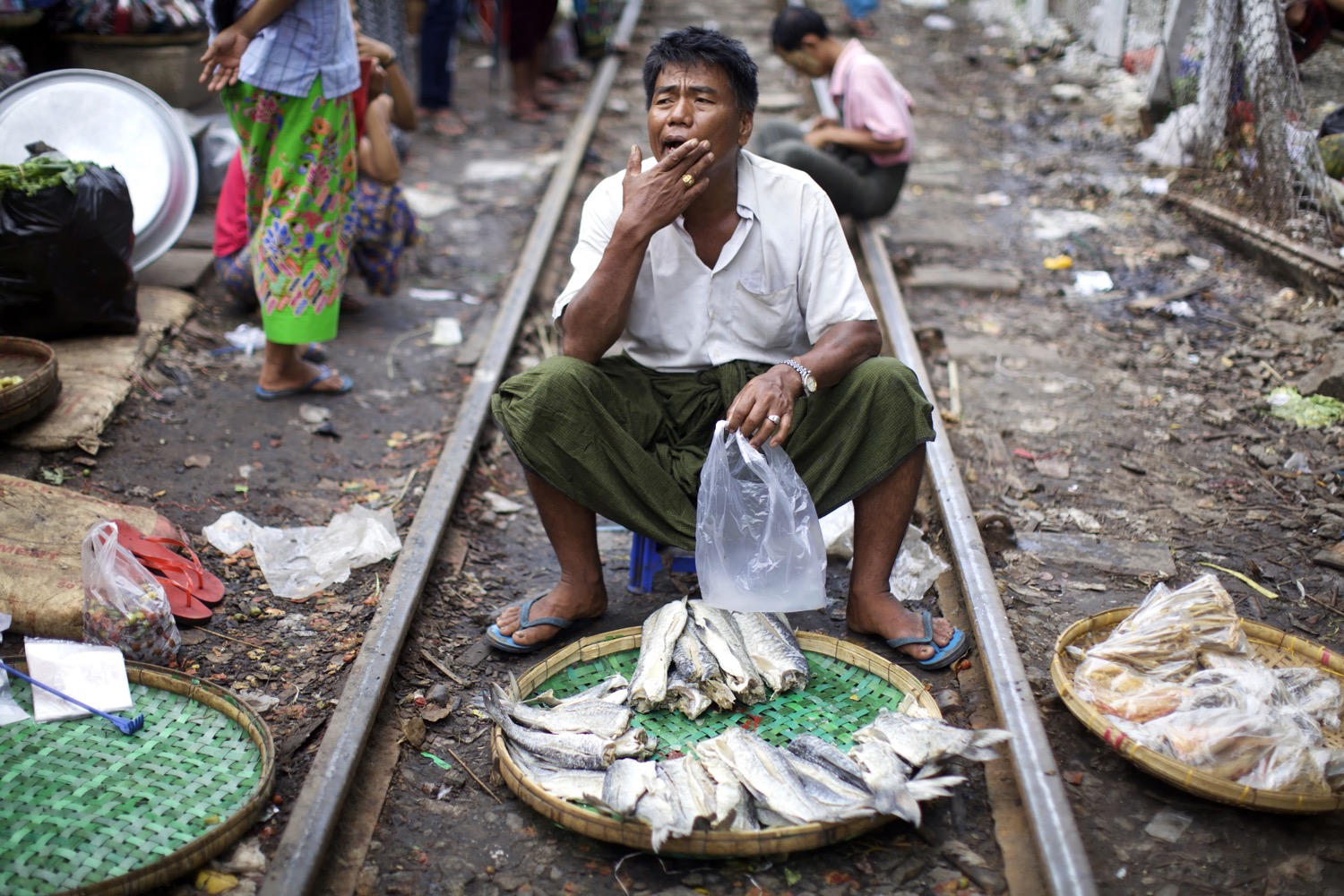 Five Essential Shots You Need to Get for Street Market Photography - man selling fish at a market on the train tracks