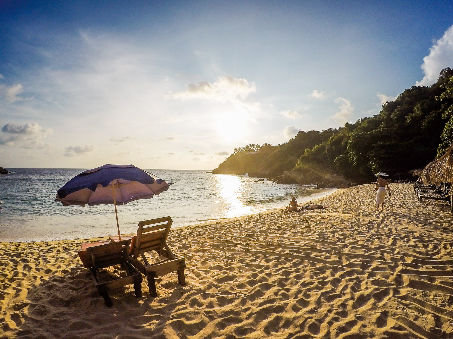 beach with chairs and umbrella - how to choose your next travel photography destination