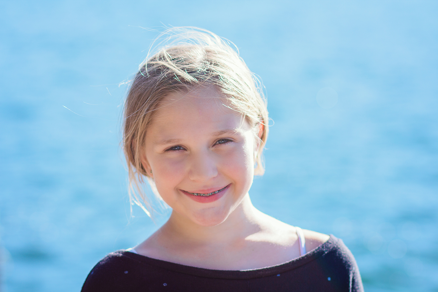 girl backlit with water in the background - 3 Tips For Photographing Kids in Harsh Light